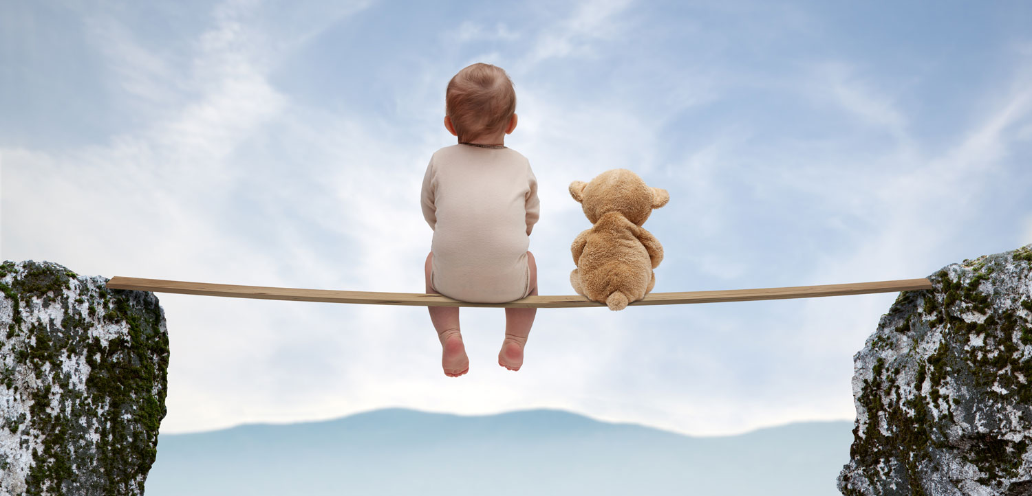 A baby boy and a teddy bear sit on a plank balanced between 2 cliffs, enjoying the view